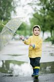 Little boy in raincoat and rubber boots playing in puddle. Happy little kid with umbrella royalty free stock photo