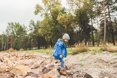 Little boy in raincoat walking. On rocks stock photography