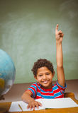 Little boy raising hand in classroom. Portrait of cute little boy raising hand in classroom Stock Photo