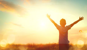 Little boy raising hands over sunset sky royalty free stock image