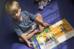 A little boy reading. His book Stock Image