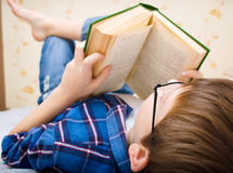 Little boy is reading a book. While laying on bed and wearing glasses Royalty Free Stock Photo