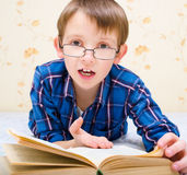 Little boy is reading a book. At home Stock Photo