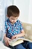 Little boy reading book Stock Photos