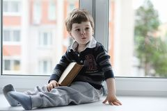 The little boy is reading a book. The child sits at the window a Royalty Free Stock Image