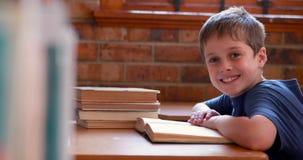 Little boy reading book in classroom. In elementary school stock video