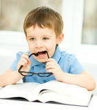 Little boy is reading a book. Cute little boy is reading book while sitting at table, indoor shoot Stock Image
