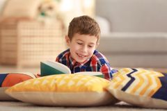 Little boy reading book on floor with pillows Royalty Free Stock Photos