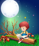 Little boy reading book in garden at night Royalty Free Stock Photography