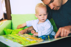 A little boy is reading a book with his father in a home interio. Rs. Father and son spend time together. Family, Childhood concept royalty free stock photos