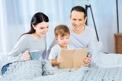 Little boy reading a book for his parents. Interesting fairy tale. Pleasant little boy sitting on the bed under the blanket and reading a book for his beloved Stock Photos