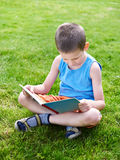Little boy reading book outdoors on grass Royalty Free Stock Photos