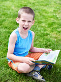 Little boy reading at book outdoors Stock Photo