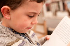 Little boy reading a book. Picture of a boy reading a book at an outside library. The book is open however the text is blurred so as to avoid any copyright and royalty free stock photo