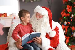 Cute boy reading book while sitting on authentic Santa Claus` lap indoors stock images