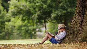 Little boy reading a book sitting at the foot of a big linden tree stock video