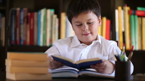 Little boy reading book with a smile stock footage
