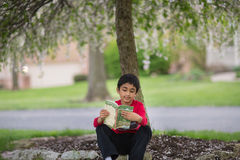 Little Boy Reading a Book Underneath a Tree. In Spring Stock Photo