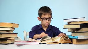 Little boy reading a different book. Blue background. Slow motion stock video footage