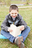 Little boy reading funny book Stock Image