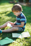 Little boy reading letter from friend Stock Photo