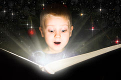 Little boy reading magic book Royalty Free Stock Images