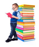 Little boy reading near big stack of books Stock Photography