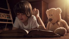 Boy reading book with his teddy bear royalty free stock photography