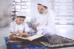 Little boy reading the Quran with his father. Portrait of cute little boy is reading the Quran with his father while sitting in the mosque stock photos