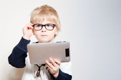 Little boy reading on tablet pc computer Royalty Free Stock Image