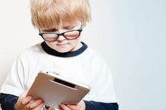 Little boy reading on tablet pc Stock Images
