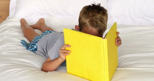 Little boy reading yellow book on bed Stock Image