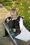Little boy reads a book. In autumn Royalty Free Stock Images