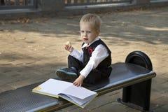 Little boy reads a book. In autumn Stock Photos