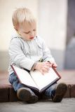 Little boy reads a book Stock Images