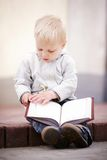 Little boy reads a book Stock Photography