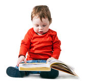 Little boy reads the book interestedly Royalty Free Stock Image