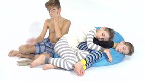 Three brothers sleeps together on the bean bag at white background