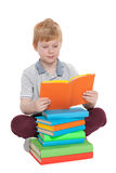 Little boy reads near the pile of books Stock Photo