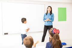 Preschool student participating in class. Little boy ready to draw on the board while playing a game in a preschool classroom stock photos