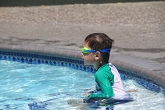 Little boy ready to swim in pool. Wearing goggles, summer day Stock Images
