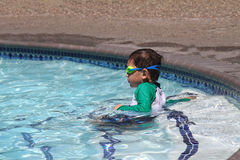 Little boy ready to swim in pool. Wearing goggles, summer day Stock Photo