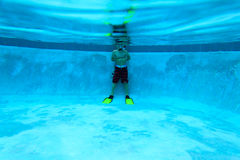Little boy ready to swim underwater in the pool stock image