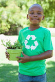 Little boy in recycling tshirt holding potted plant Royalty Free Stock Images