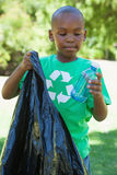 Little boy in recycling tshirt picking up trash Stock Photos