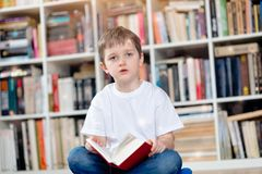 Little boy with red book in the library Stock Image