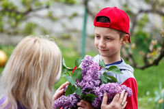 Little boy in red cap give lilac mother's day Stock Photography