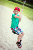 Little boy in red cap sit on swing rope Royalty Free Stock Image