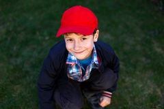 Little boy in red cap squat outdoor on grass Royalty Free Stock Image