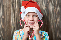 Little boy in red cap with two Christmas candy cane Stock Photography